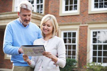 Imagem de um casal olhando planta de casa, vendendo imóvel e pensando quanto tempo leva